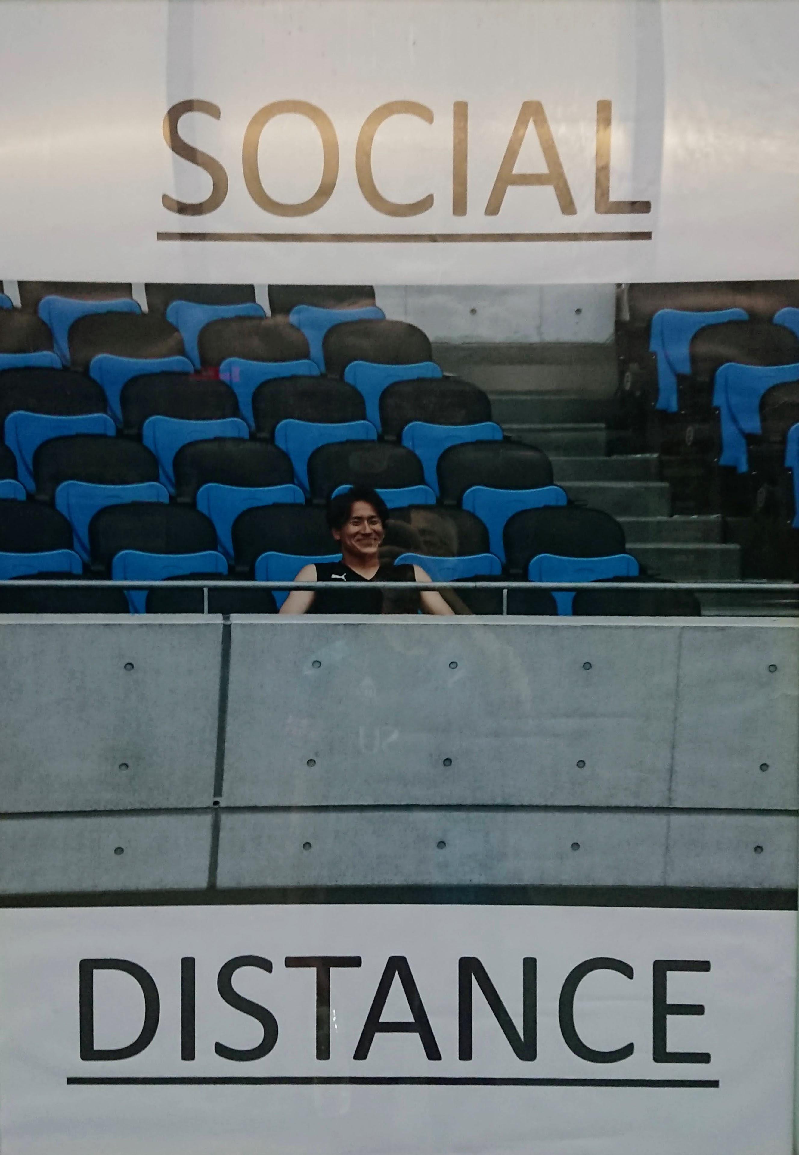 [写真]登里が一人でスタジアムのシートに座る「SOCIAL DISTANCE」のポスター